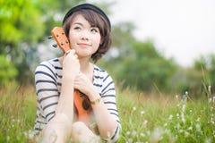 Härlig thai kvinna med ukulelen i trädgård Arkivfoto