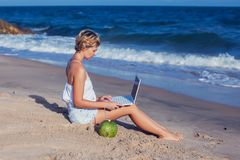 Härlig tillfällig kvinna med en bärbar dator på stranden med havet I royaltyfria bilder
