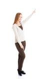 Härlig tillfällig kvinna som pekar upp och annonserar. arkivfoto