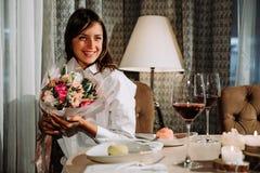 Härlig tillfredsställd kvinna med blommor som ler på kameran Arkivfoto