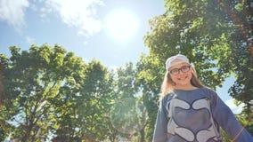 Härlig tolv-år-gammal tonåringflicka som framme poserar och rotera av en videokamera på bakgrunden av sommaren stock video