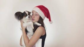 Härlig tonårig flicka i ett Santa Claus lock och en hund kontinentala Toy Spaniel Papillon som kysser och omkring på bedrar joyfu stock video