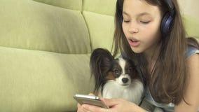 Härlig tonårig flicka i hörlurar som sjunger karaokesånger i smartphone med hunden Arkivbilder