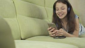 Härlig tonårig flicka i hörlurar som sjunger karaokesånger i video för smartphonemateriellängd i fot räknat stock video