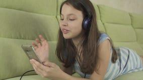 Härlig tonårig flicka i hörlurar som sjunger karaokesånger i video för smartphonemateriellängd i fot räknat arkivfilmer