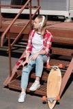 härlig tonårig flicka i röd plädskjorta och hörlurar som sitter på trappa royaltyfri fotografi