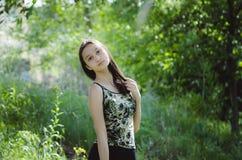Härlig tonårig flicka på en grön trädbakgrund royaltyfria bilder
