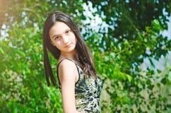 Härlig tonårig flicka på en grön trädbakgrund royaltyfri fotografi
