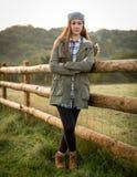 Härlig tonårig flickabenägenhet mot ett lantgårdstaket Arkivfoton