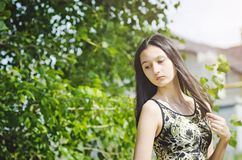 Härlig tonårig flickabrunett med långt hår på en bakgrund av gröna träd royaltyfria bilder