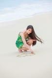 Härlig tonårig flickateckningshjärta i sand på den tropiska stranden royaltyfri bild