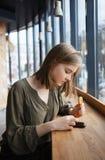 Härlig tonårig studentflicka? oncentrated uppmärksamhet genom att använda smartphonen för internet som surfar på gatakafét som si Arkivfoto