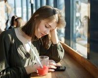 Härlig tonårig studentflicka? oncentrated uppmärksamhet genom att använda smartphonen för internet som surfar på gatakafét som si Royaltyfria Foton