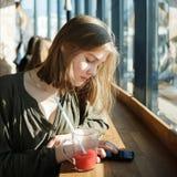 Härlig tonårig studentflicka? oncentrated uppmärksamhet genom att använda smartphonen för internet som surfar på gatakafét som si Royaltyfri Fotografi