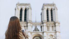 Härlig tonåringkvinnlig som tar foto av Notre Dame på retro filmkamera i Paris, Frankrike, berömd domkyrka lager videofilmer
