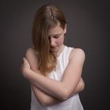 Härlig tonårs- flicka i den vita klänningen som omfamnar sig Fotografering för Bildbyråer