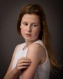 Härlig tonårs- flicka i den vita klänningen som omfamnar sig Arkivbild