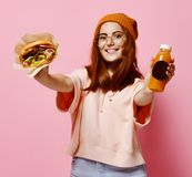 Härlig tonårs- flicka med den röda den hår- och hattinnehavhamburgaren och drycken i båda händer royaltyfri foto