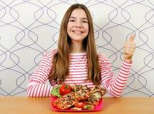 Härlig tonårs- flicka med smörgåsen och den ok tummen upp royaltyfria foton