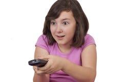 Härlig tonårs- flicka med tvfjärrkontroll i henne händer Royaltyfria Bilder