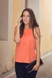 Härlig tonårs- flicka på mobiltelefonen i stadsgatan. Royaltyfri Bild