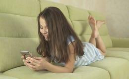 Härlig tonårs- flicka som har gyckel som meddelar på smartphonen Arkivfoto
