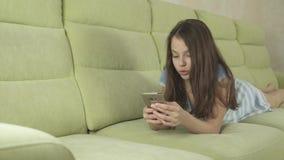 Härlig tonårs- flicka som har gyckel som meddelar på videoen för smartphonemateriellängd i fot räknat stock video