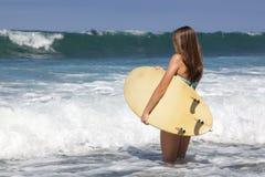 Härlig tonårs- flicka som rymmer en surfingbräda på le för strand Arkivfoton