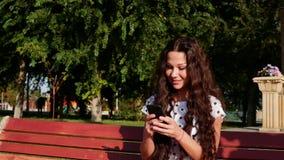 Härlig tonårs- kvinna av ett Caucasian utseendemässigt användande smart sammanträde för telefonteknologiapp på gator för en bänks stock video