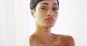 Härlig topless afrikansk kvinna som ser kameran och spelar med gardiner royaltyfria foton