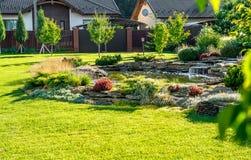 Härlig trädgårdlandskapdesign Sikten av färgrika träd och dekorativa klippte buskar vaggar Royaltyfria Bilder