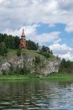 Härlig träkristen ortodox kyrka på banken av ret Royaltyfria Bilder