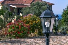 H?rlig traditionell europeisk lantlig borgg?rd med lyktor och blomningv?xter royaltyfri fotografi