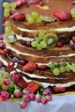 Härlig tre-lager bröllopstårta med jordgubbar och hallon Arkivfoton