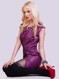 Härlig trendig blond flicka i den violetta klänningen Fotografering för Bildbyråer