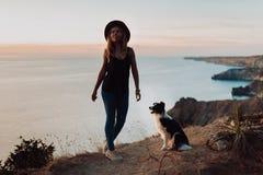 Härlig trendig flicka på en klippa vid havet med en hund border collie arkivbilder