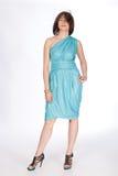 Härlig trendig kvinna i turkosklänning. Arkivbild