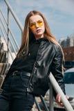 Härlig trendig ungeflicka med långt hår i gul solglasögon i stad, arkivfoto