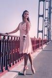 Härlig trevlig ung kvinna som trycker på balustraden royaltyfria foton