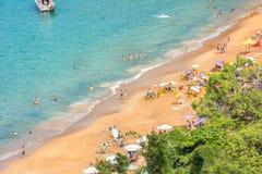 Härlig tropisk strand många personer på en solig dag, blått hav royaltyfria foton