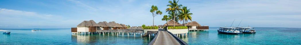 Härlig tropisk strandpanorama av bungalos med bron nära havet med gömma i handflatan träd och fartyg på Maldiverna Royaltyfri Fotografi