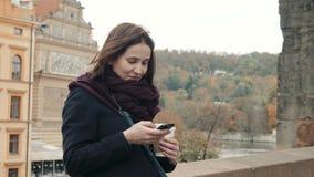 Härlig turist för ung kvinna i Prague genom att använda hennes Smartphone, resande begrepp fotografering för bildbyråer