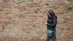 Härlig turist för ung kvinna som går och använder hennes Smartphone, resande begrepp royaltyfri bild