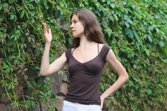 härlig tyckande om flickanatur Den unga kvinnan beskådar växten Royaltyfria Foton
