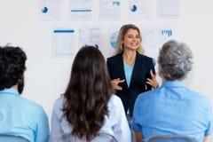 Härlig tysk affärskvinna med blont hår som ger presentation till kollegor arkivfoto