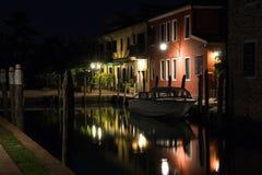 Härlig tyst aftoncityscape av den Burano ön i Venedig Färgade byggnader exponeras av gataljus reflekterade i en wa royaltyfri foto