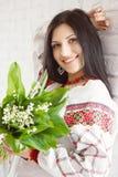 Härlig ukrainsk flicka i nationell klänning med buketten av flowe royaltyfri foto
