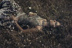 Härlig ung östlig flicka i etniska smycken som ligger på gras Arkivbilder