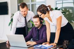 Härlig ung affärskvinna och businessmans i hörlurar med mikrofon genom att använda bärbara datorer, medan arbeta i regeringsställ royaltyfria foton