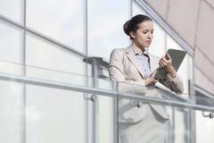 Härlig ung affärskvinna som använder den digitala minnestavlan på kontorsräcket arkivbild
